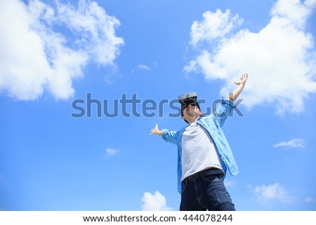 Smile happy man getting experience using VR-headset glasses of virtual reality with sky and cloud background, asian male