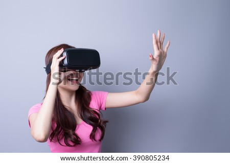Smile happy woman getting experience using VR-headset glasses of virtual reality at home much gesticulating hands, asian beauty - stock photo