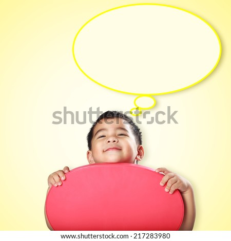 Smile little asian boy with empty think bubble on yellow background - stock photo