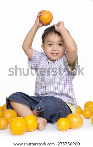 Smile little boy sitting floor holding oranges - stock photo
