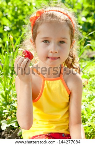 Smile little girl in summer day with strawberries