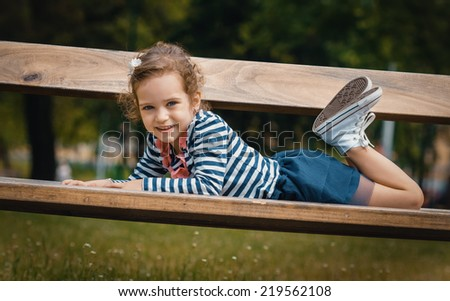 Smile little girl lying on bench in a park, relaxing in the nature - stock photo
