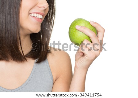 Smile of healthy happiness. Cropped shot of a young beautiful woman smiling holding an apple - stock photo