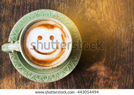 Smile of latte coffee with sunshine on wooden background.(Top view) - stock photo