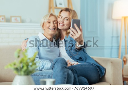 Smile. Positive cheerful aged woman looking happy while being at home and taking a photo with her smart enthusiastic granddaughter with a help of a modern gadget