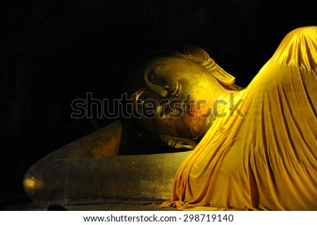 smile reclining buddha statue in nirvana position at Cave, Phetchaburi, Thailand - stock photo