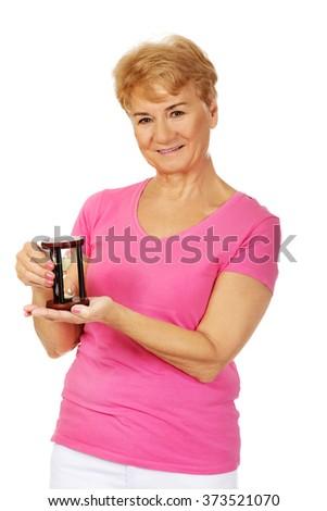 Smile senior woman holding sandglass - stock photo