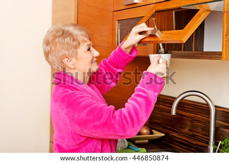 Smile senior woman taking mug from a kitchen cabinet