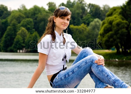smile teen sitting on bench in summer green park
