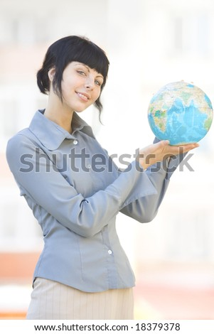 smile woman with globe near white building - stock photo