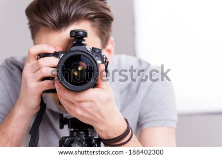 Smile! Young man focusing at you with digital camera while standing in studio with lighting equipment on background  - stock photo