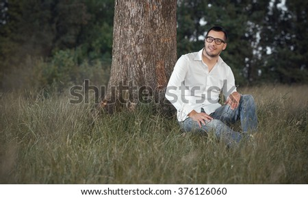 Smile young man sit on grass in nature. Full body, outdoors. Copyspace - space. Positive friendly guy - stock photo