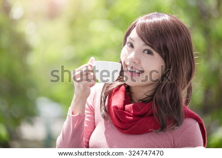 smile young woman holding cup of coffee or tea and wearing winter clothing with green background, asian beauty - stock photo