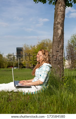 Smile young woman searching in computer at the park - stock photo