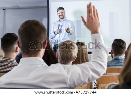 Smiled lecturer are explaining something to his students. One of them is raising a hand to ask a question