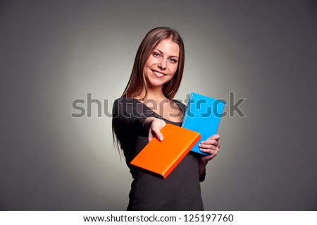 smiley alluring woman giving the book. studio shot over dark background - stock photo