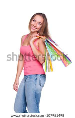 smiley alluring woman with shopping bags posing over white background