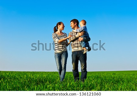 smiley and cheerful family walking at the green field - stock photo