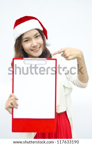 Smiley Asian woman in santa hat hold a red writeboard. isolated on white background