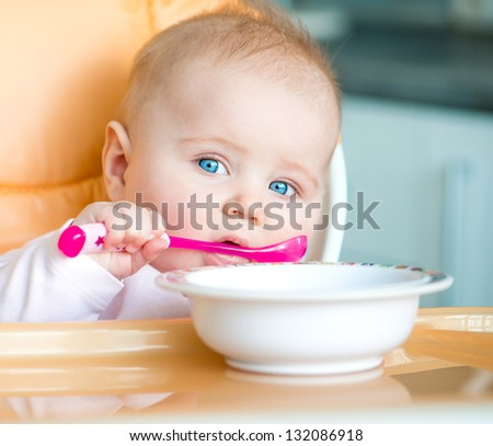 smiley baby girl is holding a spoon in her mouth and going to eat - stock photo