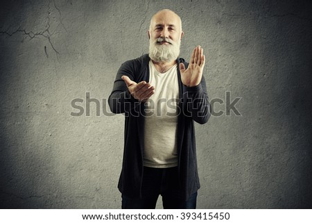smiley bearded man clapping and looking at camera over dark background - stock photo