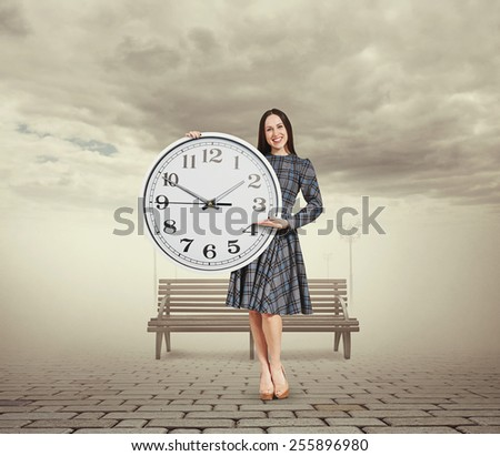 smiley beautiful woman holding big clock and pointing at the time. photo in foggy park - stock photo