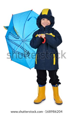 Smiley boy is holding attractive umbrella dressed up in raincoat and rainboots shot in studio on white background