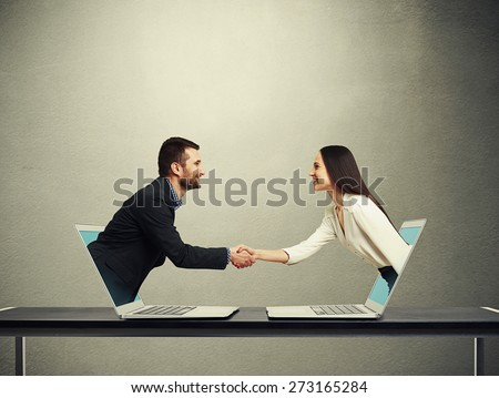 smiley businessman and businesswoman come out from laptop, shaking hands and looking at each other over dark grey background - stock photo