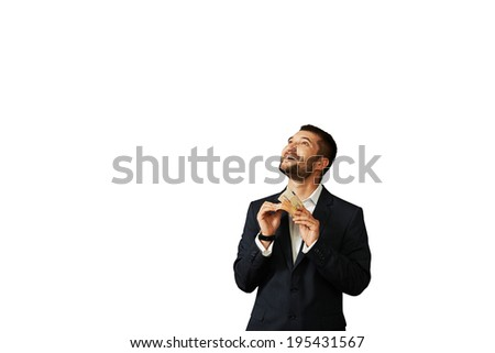 smiley businessman counting money and looking up at empty white copyspace