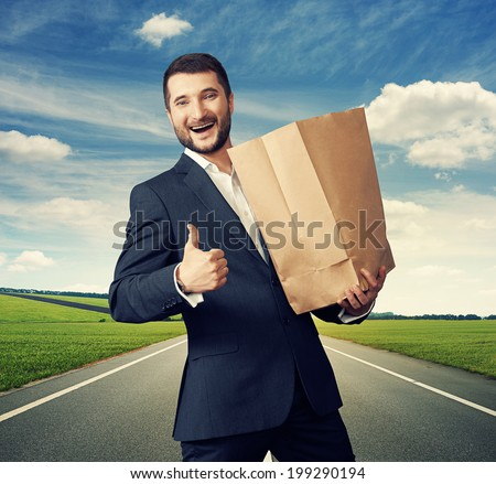 smiley businessman holding paper bag and showing thumbs up at outdoor - stock photo