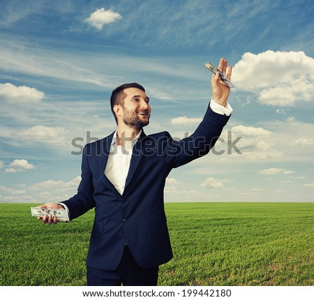 smiley businessman holding paper money at outdoor