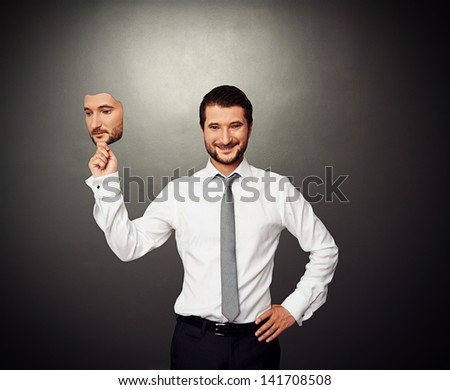 smiley businessman holding serious mask over dark background - stock photo