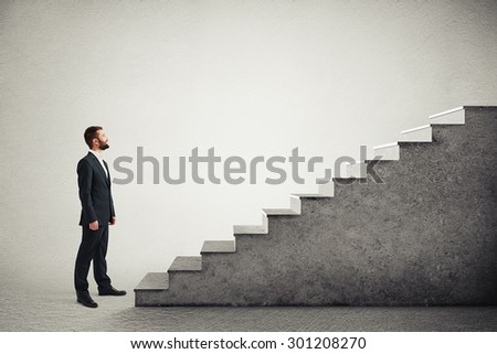 smiley businessman in formal wear standing near concrete stairs and looking at the top over light grey background - stock photo