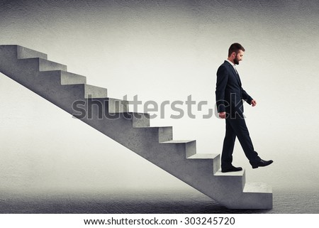 smiley businessman in formal wear walking down the steps over grey background