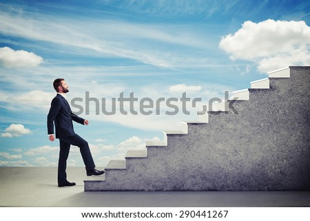 smiley businessman in formal wear walking up stairs over blue sky