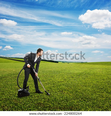 smiley businessman vacuuming green grass at outdoor - stock photo