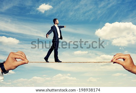 smiley businessman walking on the rope at outdoor - stock photo