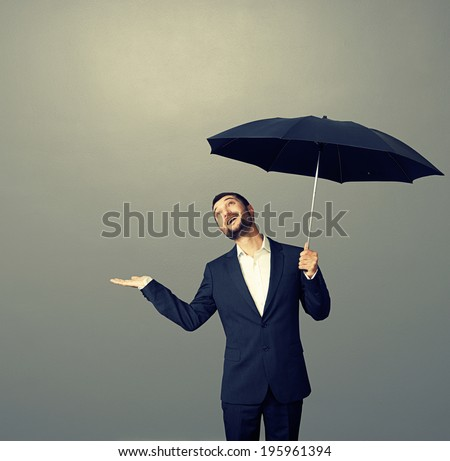 smiley businessman with umbrella looking up dark background