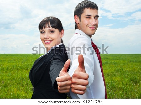smiley businesspeople showing thumbs up over green grass and blue sky - stock photo