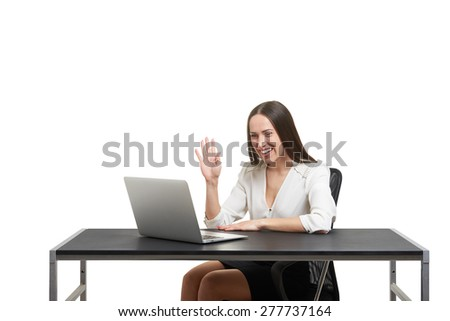 smiley businesswoman have video chat, waving her hand and looking at laptop over white background - stock photo