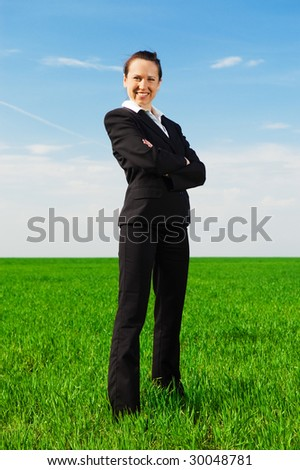 smiley businesswoman standing at the green grass