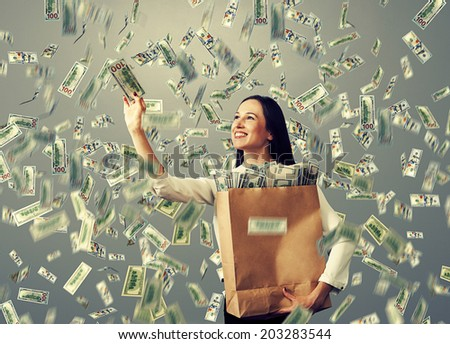 smiley businesswoman with paper bag catching money under dollar's rain - stock photo