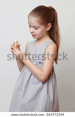 Smiley caucasian little girl holding ceramic toy rabbit on Easter holiday - stock photo