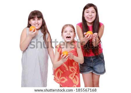 Smiley cheerful positive little girls holding mandarins isolated over white/happy little girls with orange mandarin