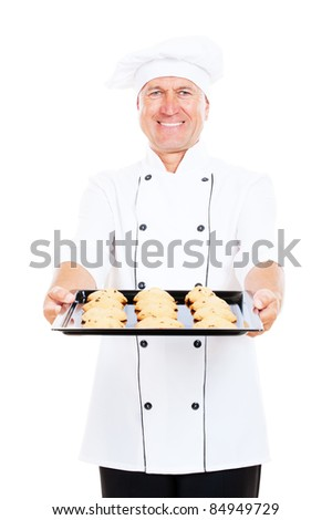 smiley cook holding baking tray with cookies. isolated on white background