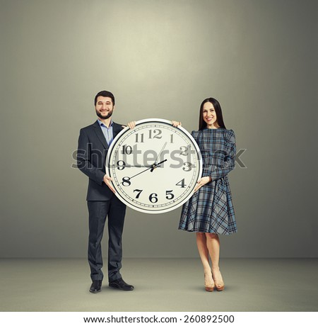 smiley couple with big white clock over grey background