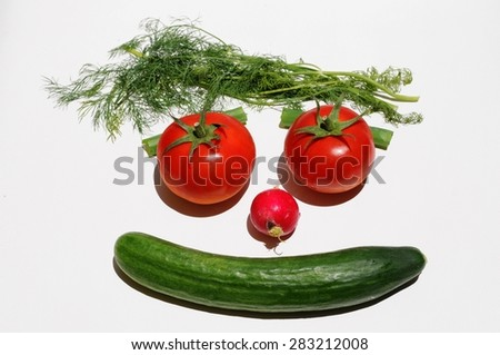 Smiley face made of vegetables - tomatoes, cucumber, radish and dill herbs on white background - stock photo