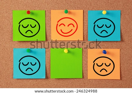 Smiley Face sticky notes pinned on cork. - stock photo