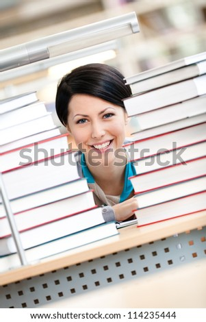 Smiley female student is looking over the books sitting at the table