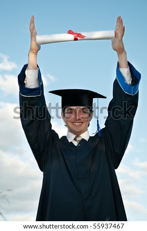 smiley graduate student in cloak holding a diploma over his head outdoors - stock photo